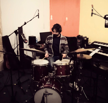 Andrea Scala sitting as his drums during a recording session at his studio